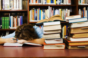 Exhausted Student Falling Asleep While Cramming --- Image by © Randy Faris/Corbis
