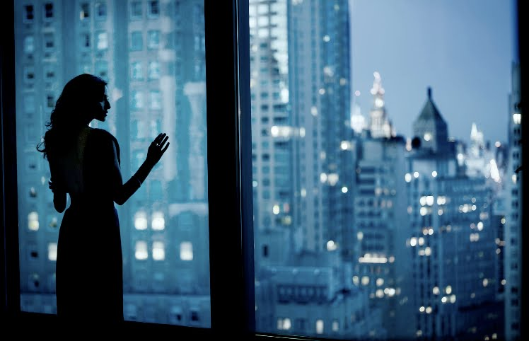 woman-looking-out-windows-urban-city-view-skyscrapers-evening-night-blue-black-white_troy-house-photography